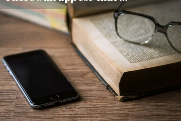 Image of a smartphone, and reading glasses sitting on a book