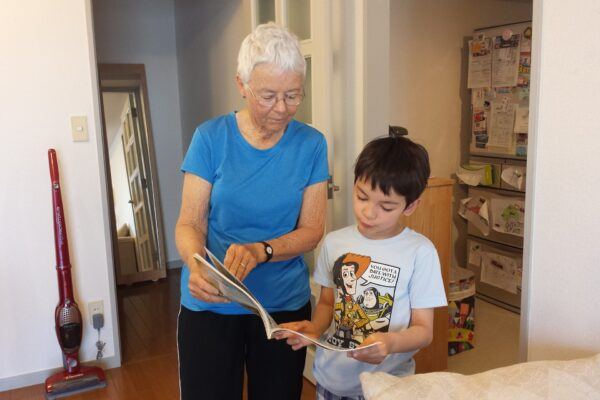 a grandmother helps her grandson fill out a questionnaire on family medical history